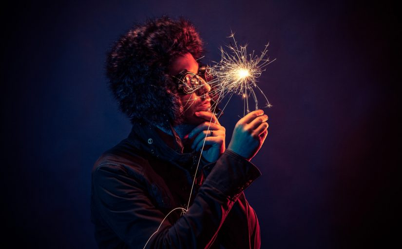 Man in glasses and hat looks at sparkler