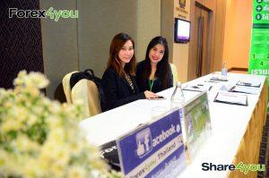 2 เจ้าหน้าที่ Forex4you ยิ้มให้กับคุณที่โต๊ะลงทะเบียนในงานสัมมนาประเทศไทย