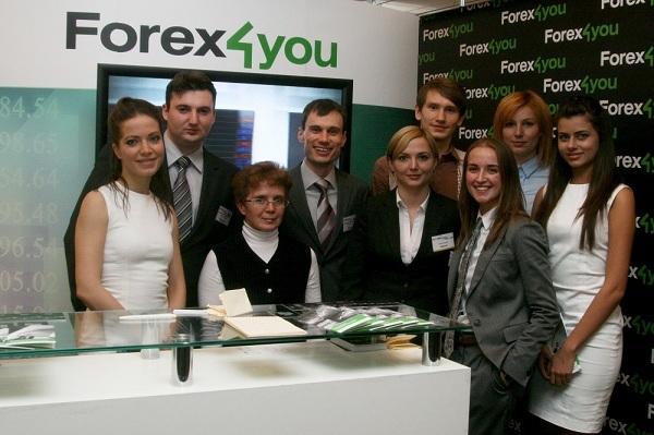 เจ้าหน้าที่ Forex4you ยืนข้างบู๊ทของบริษัทที่งาน Moscow Expo พฤศจิกายน 2011